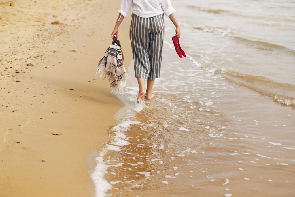 Woman walking barefoot on beach